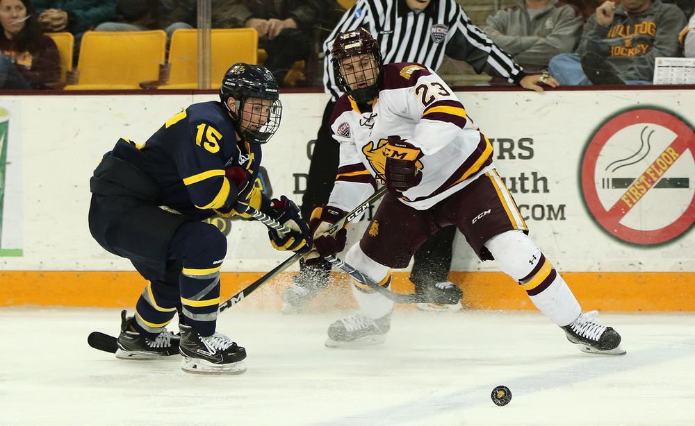 freshman forward Nick Swaney battles for a loose puck with a Merrimack defender