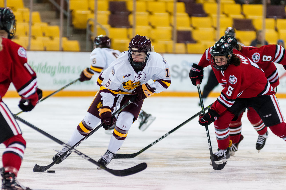 Sophomore forward Reagan Haley (15) advances the puck into the Huskies' zone. Photo by Alex Ganeev.
