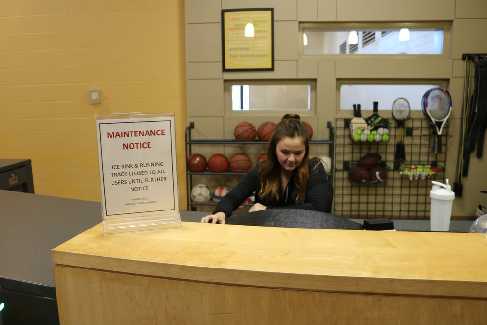 RSOP student worker Haley Loney sits next to the Facilities Management's notice and lets students know that the ice rink and track is closed. Photo by Samantha Church