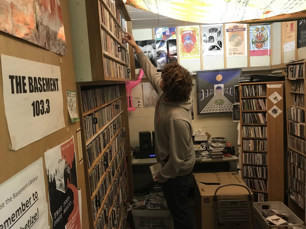 Finnegan looks through the KUMD library to decide what he plays on the radio. Photo by: Vincent Harvieux