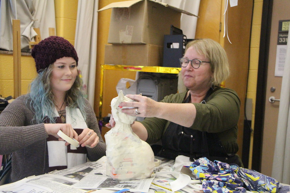 Alison Aune and Sawyer Jacobson, a transfer student, create a cat from recyclables. Photo by Jakob Bermas