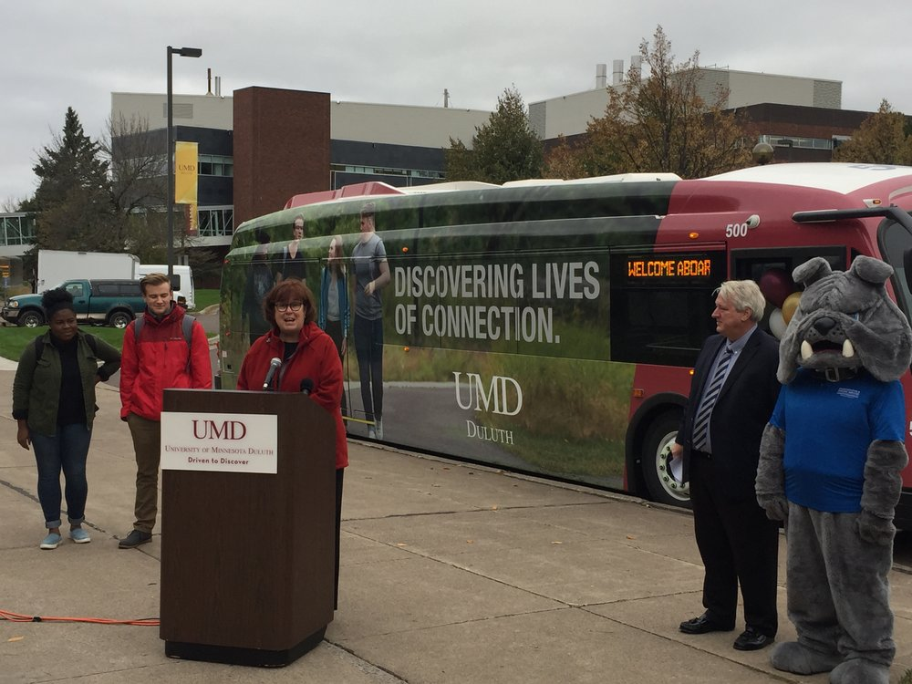 Lisa Erwin, the Vice Chancellor for Student Life and Dean of Students, leads the unveiling of the new electric bus. Pictured with Champ, students featured on the bus, and DTA General Manager Phil Pumphrey. Photo courtesy of Corbin Smyth.