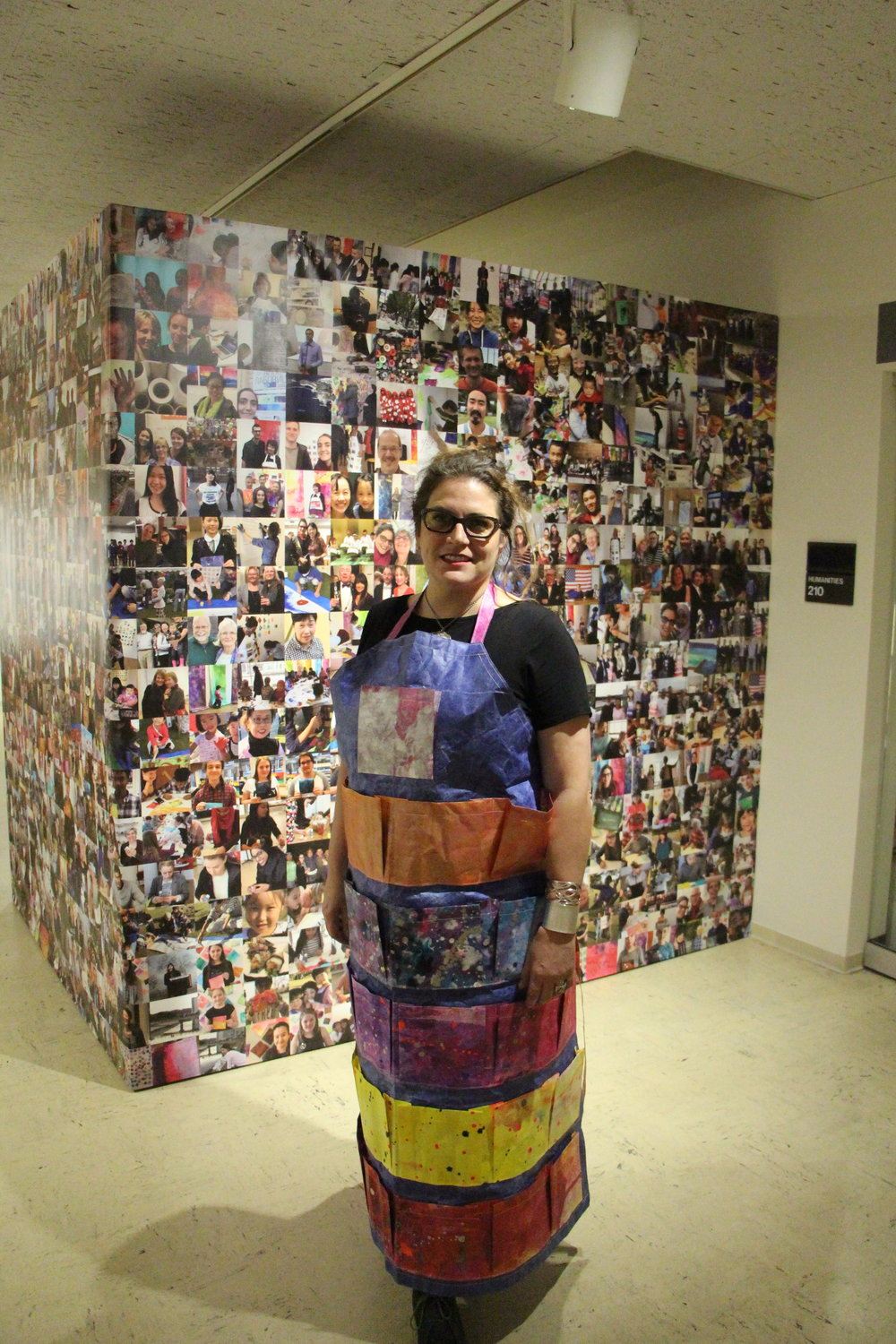 """Labovitz wearing a """"celestial generosity apron"""" standing in front of pictures from her art workshops. Photo by Jakob Bermas"""