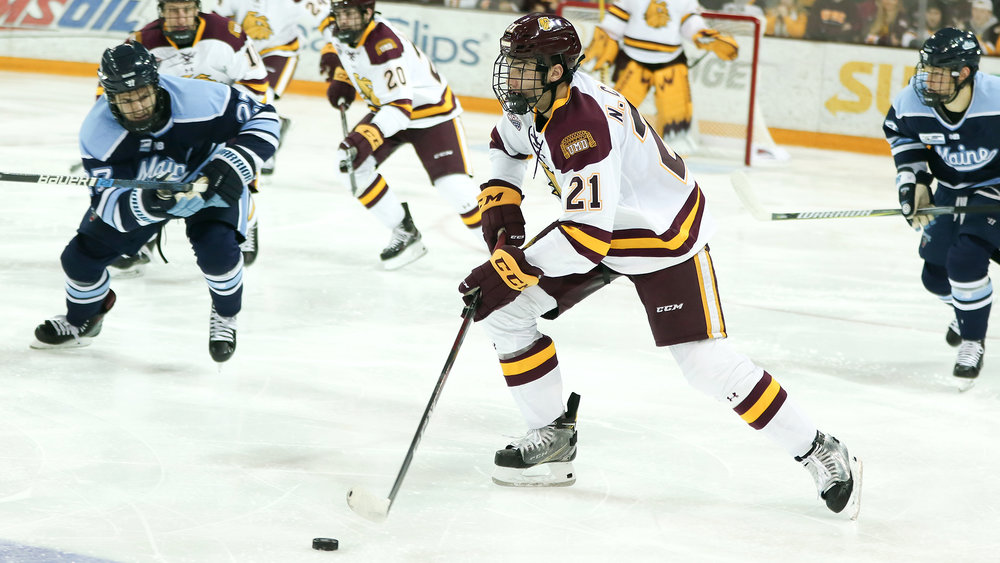 Noah Cates (21) controls the puck for the Bulldogs. Photo courtesy of UMD Athletics.