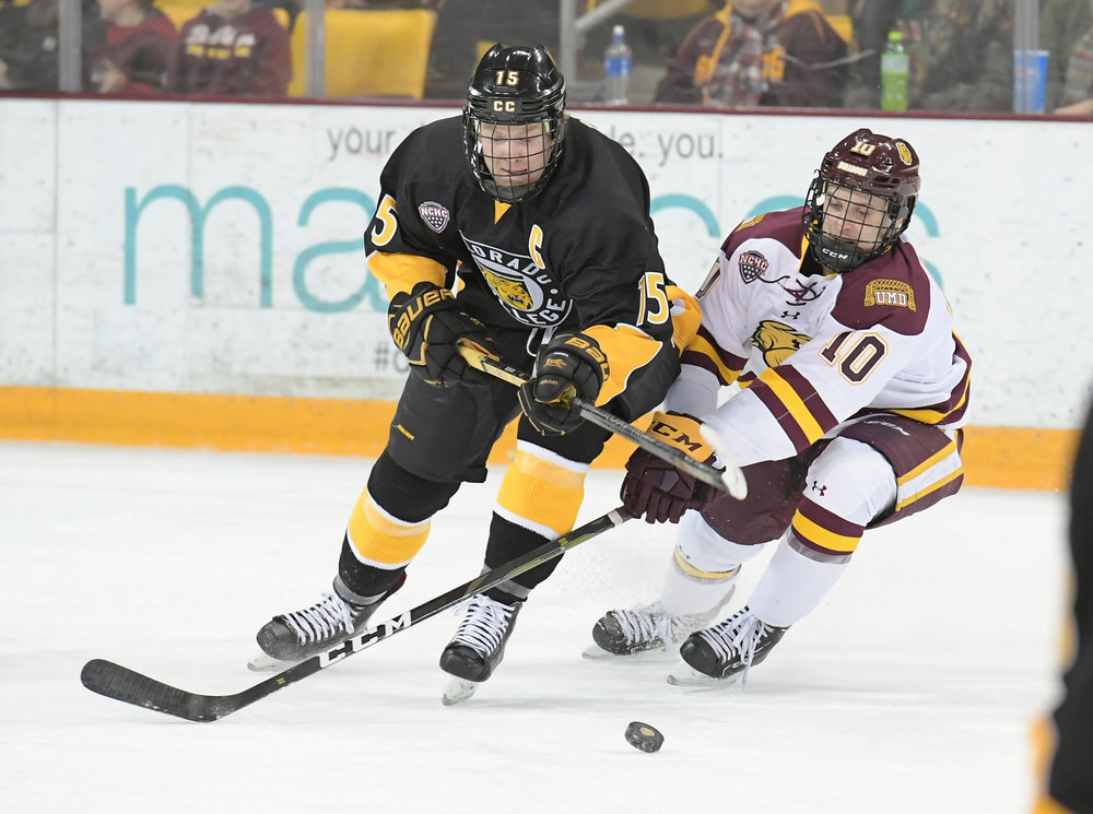 UMD sophomore Kobe Roth (10) fights for the puck against Mason Bergh (15). Photo courtesy: UMD Athletics
