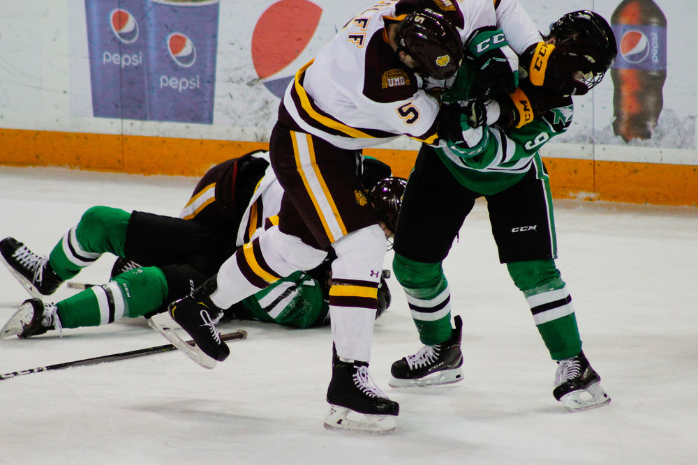 Nick Wolff (5) scuffles with Dixon Bowen (9) in the second period. Photo by: Morgan Pint