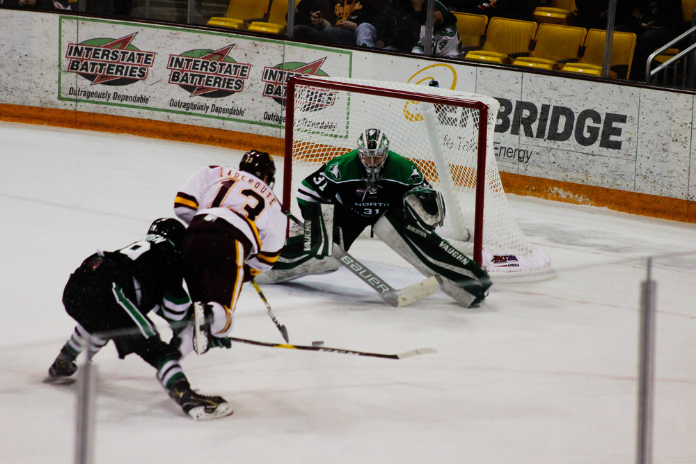 UMD freshman Tanner Laderoute (13) looks to score versus UND freshman goalie Adan Scheel at AMSOil. Photo by: Morgan Pint