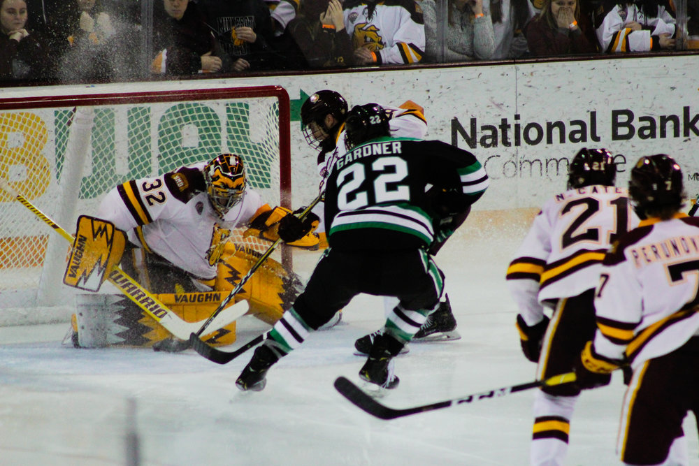 Shepard (32) makes one of his 28 saves off the shot by North Dakota forward Rhett Gardner. Photo by: Morgan Pint