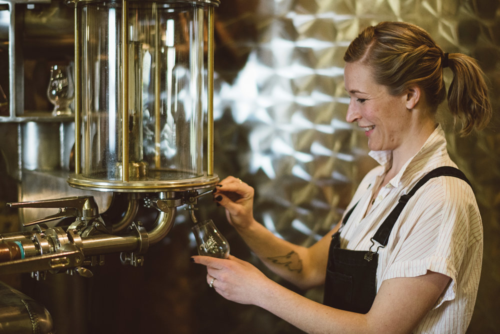 Co-owner, Emily Vikre, pouring a glass of spirits at The Vikre Distillery. Photo courtesy of Vikre Distillery