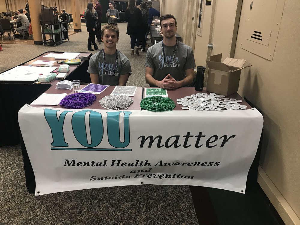 YOUmatter members Jackson Eidsvold (left) and Luke Houska (right) welcome students to a YOUmatter event. Photo courtesy of Kalynn Tilton
