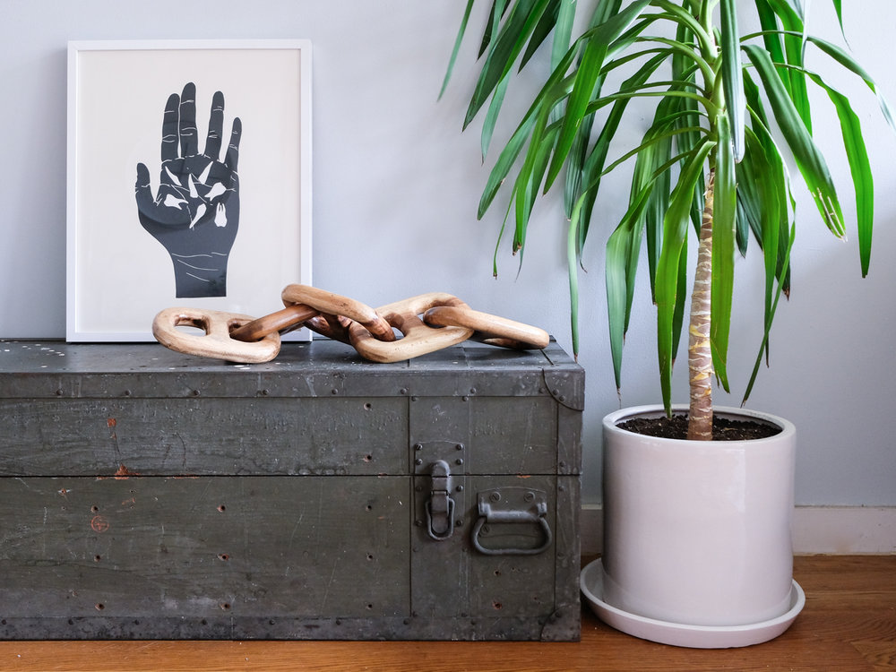 While living in this apartment, I bought a few decor items including this chain. Chains are a    big trend that I see in decor right now   . I thrifted this old trunk to add additional seating and storage to our living room.