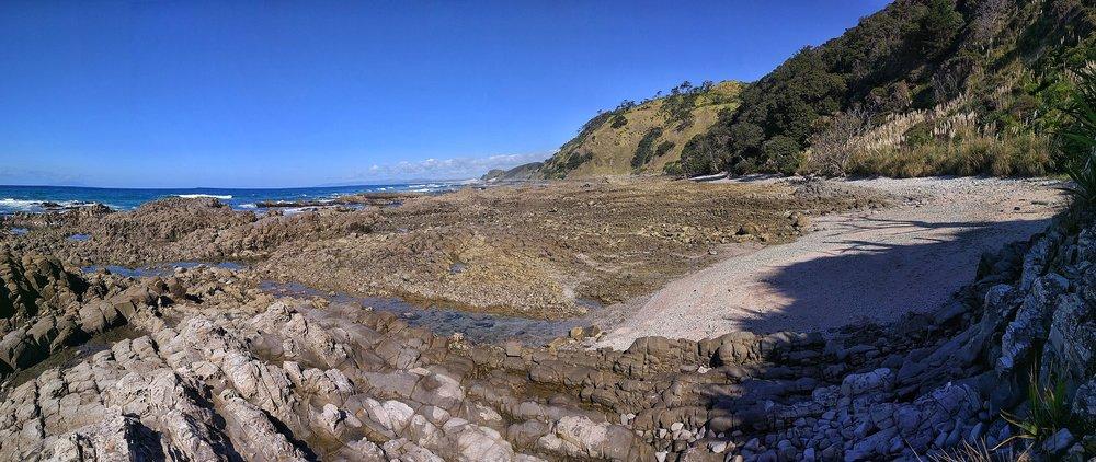 Walking on rocky terrain on the water level part of Mangawhai Walkway