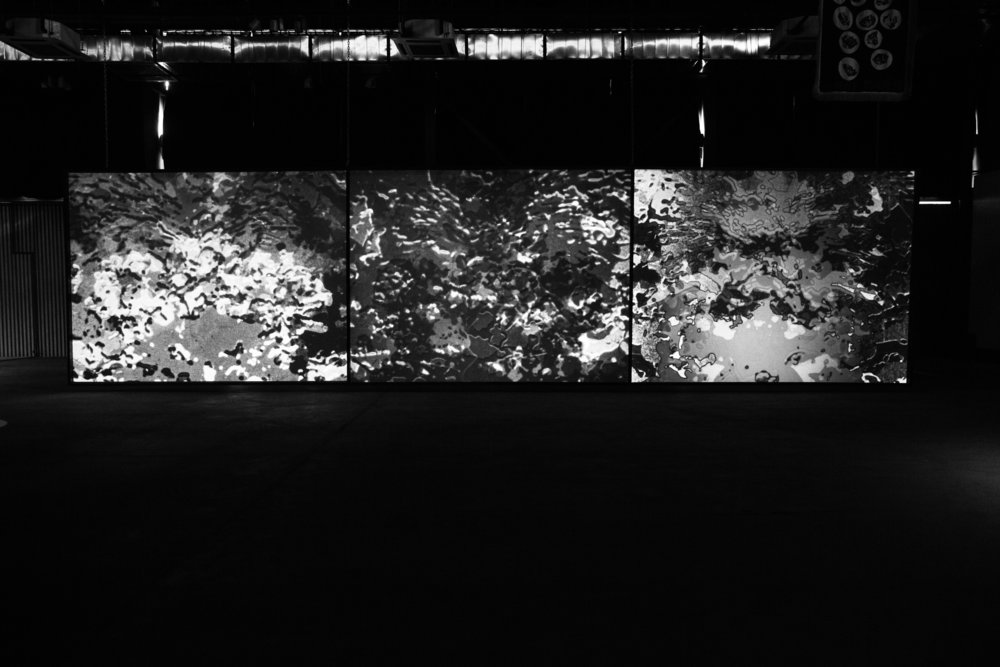 "- 轻身而出Easy Out 三屏幕投影装置 3 Channel Video Installation16 毫米电影转数字16 mm Transferred to Video 9'1971 由 Cherry and Martin 画廊支持 Courtesy of Cherry and Martin 作品《轻身而出》中对于布尔乔亚情景的幽默式颠覆,以及对强迫式图像的指涉, 都表达了向另一先锋艺术经典作品、布努埃尔和达利的《一条安达鲁狗》(1928) 的致敬。比如在奥尼奥作品中,某个单调的郊区十字路口被巨蚁侵袭,巨蚁的身影重重叠加在画面之上。除此之外,他也抛出了诸如""与此同时"" ""几天之后""之类有荒诞而超现实色彩的字幕——这是阻挡线性叙事的护符,也是中产色彩景观的传播媒介。或许奥尼奥作品中断裂序列的叠加手法,更深层次地表现了作品的超现实性,这 一过程也伴随着一种虚构的 ""随机接龙"" 感——这是室内游戏的一种延伸,在游戏中,一连串的艺术家共同依次进行一张人像的创作,但他们都不知道前一个人 所画的内容是什么。达利和布努埃尔在撰写《一条安达鲁狗》的脚本时,也曾依赖于某种类似的""精神自动"":""当合作者认为某个画面或者想法是源自于记忆或某种文化规律,或仅仅是有意识地与先前的某个想法有关时,他们二人便迅速摈弃它。""""《轻身而出》中的图像流跟奥尼奥大多数作品中一样,让人感觉如同一系列的微 影像被嫁接到了某个纤薄的主题性架构上,这有点像某个动态的、单人完成的随机接龙。《下沉气流》充满着不讨人喜欢的度假镜头, 这也极大地来源于先前影片中充斥的画面,并标志着与非都市环境的空间悖论感和非对称性所发生的新的 碰撞。此处和他处一样,人迹黯去之后,惟余湿润和贫瘠的风景。伸出车窗拍摄的频繁的动态镜头,正是奥尼奥屏幕作品之瞬时性的完美象征。""《下沉气流》驾轻就熟地发挥了观光片和家庭录影所具有的非虚构类符号,将文 本间的关系推进到一种广袤的、看起来充满敌对性的竞技场。据称他的影片在运 用深奥的影视技术方面别具一格;尽管如此,把他的作品降格为""粗制滥造""的、 无拘无束而超然的纯主观作品也是不可能的。任何的电影性元素在奥尼奥的眼中 都不算新鲜。他闪躲着形式主义还原论的圈套,但也并不安于置身于后现代讽刺 性集成的标题之下,他的作品盘桓于""与世隔绝的冷漠""和""针锋相对的论战""的两 极之间。Easy Out pays homage to yet another avant-garde classic, Buñuel and Dalí's Un Chien andalou (1928), by way of humorous subversions of bourgeois settings and allusions to obsessional images, such as O'Neill's superimposition of giant ants overrunning a humdrum suburban intersection. For good measure, he tosses in some nonsensical Surrealist subtitles: ""Meanwhile"", ""Several days later""–talisman displayed to ward off linear narrative, the vehicle of middle-class spectacle. Perhaps a deeper bond to Surrealist aims is manifest in O'Neill's accretion of disjunct sequences, a process with parallels to the fabled ""Exquisite Corpse"". Extending the intellectual parlor game, in which a figure drawing is produced by successive artists without knowledge of what was previously drawn, Dalí and Buñuel relied on ""psychic automatism"" for the scripting of Un Chien andalou: ""When an image or idea appeared the collaborators discarded it immediately if it was derived from remembrance, or from their cultural pattern or"