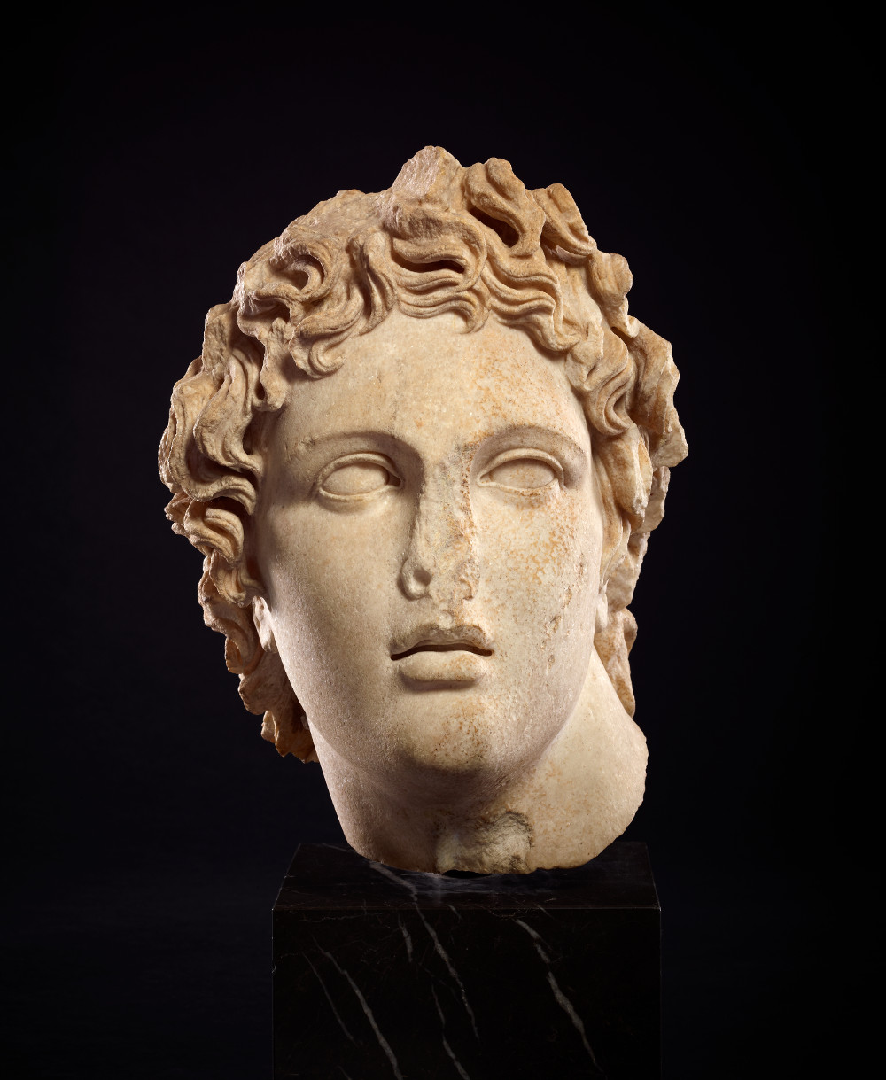 Head in the style of Alexander  - MarbleAD 100–200Roman (probably a copy of Greek work of about 330–300 BC)British Museum Alexander the Great (reigned 336–323 BC) ruled from Egypt to the Indus. He was adept at using his own image as a tool of political propaganda. He commissioned heroic portraits designed to project his character and virtues. This vision of the ruler-hero was copied by later rulers, including several Roman emperors. Their characteristics may be recognised in this idealised head with its lion's mane-like hair, clean-shaven face, full lips and tilted neck.