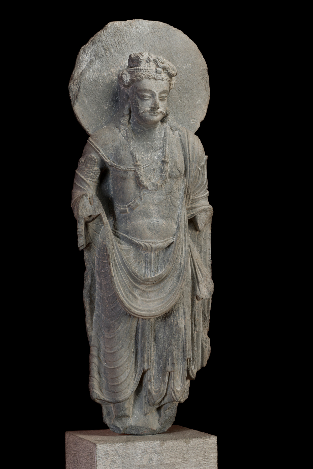 Bodhisattva Maitreya  - Grey schistAD 120–200Gandhara, Pakistan or AfghanistanGovernment Museum and Art Gallery, Chandigarh, India This sculpture of the Bodhisattva Maitreya – the Buddha to be who will succeed Gautama – is an amalgamation of many cultures. The robes are drawn from Greek art traditions, the shape of the moustache and eyes hint at Central Asian ideals of beauty, while the Buddhist iconography originates in India. Strength is communicated by his musculature, strong jaw and noble expression; spirituality through the meditative eyes and by the kamandalu, the water pot carried by wandering ascetics in India.