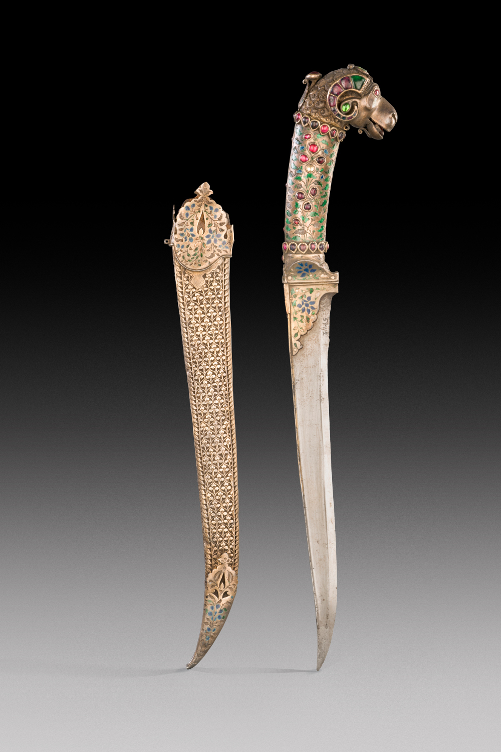 Enameled dagger - Steel, ivory, wood, gilded, inlaid with rubies and emeraldsAD 1720–1770Rajasthan, IndiaNational Museum, New Delhi The subject of the painting on this shield is Maharana Sangram Singh II – ruler of the Rajput court of Mewar from 1690 to 1734. He is shown practicing his archery, hunting tigers, and having amorous encounters in the forest, while the women of the court expectantly await his return. Messengers would carry a royal shield to allow them a safe and speedy passage, and in Rajput courts they had long been used as trays for royal gifts. The elegant dagger is of a type that was comfortably worn tucked in the sash-belt and could have been used by either a man or woman.
