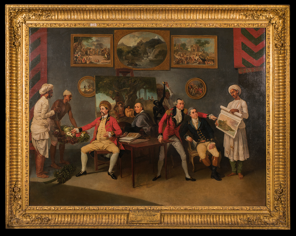 Johann Zoffany with Colonel Polier, Claude Martin and John Wombwell  - By Johann ZoffanyOil on CanvasAbout 1786–87Victoria Memorial Hall, Kolkata (R2066) The artist Johann Zoffany has shown himself here turning to look at the viewer. Alongside him are John Wombwell of the British East India Company and the Calcutta Mint, Antoine Polier, a collector of Sanskrit and Persian manuscripts, and Major General Claude Martin of the British Army. All three Europeans were invested in gathering knowledge about India. On the walls behind them, paintings of tropical landscapes populated by locals illustrate the grand project of the Enlightenment – knowledge gathering, which would also lead to colonial control.