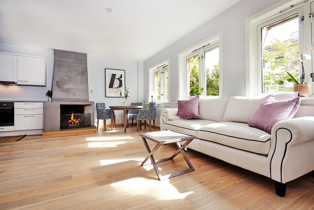 modernliving room design with white  sofa and burning fireplace