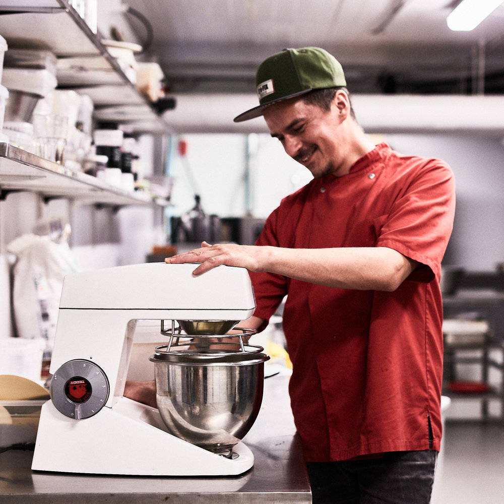 Manden bag mesterværkerne - John er geniet bag vores smukke og velsmagende kager.Med mere end 10 års erfaring som bager og kok er der god grund til, at Johns mesterværker ikke er til at sætte en finger på. Når John bager i køkkenet under kaffebaren på Jagtvej, er det ikke kun de gode dufte, der spreder sig - det gør den gode karma også.John er nemlig altid i godt humør og klar med en joke eller en kæk kommentarKvalitet og opfindsomhed går hånd i hånd i Johns bageri, og man ved aldrig helt, hvad han finder på. John mestrer alt fra cheesecake i alle afskygninger til vegansk banankage og glutenfri polenta-kage.Og ikke mindst den klassiske lemonpie med marengs, som ingen laver lige så godt som John...