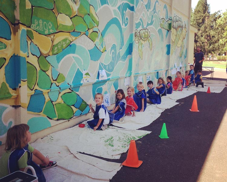 Local Eugene Muralist, Bayne Gardner, guides a group of students in the Emerald Park Mural Project.