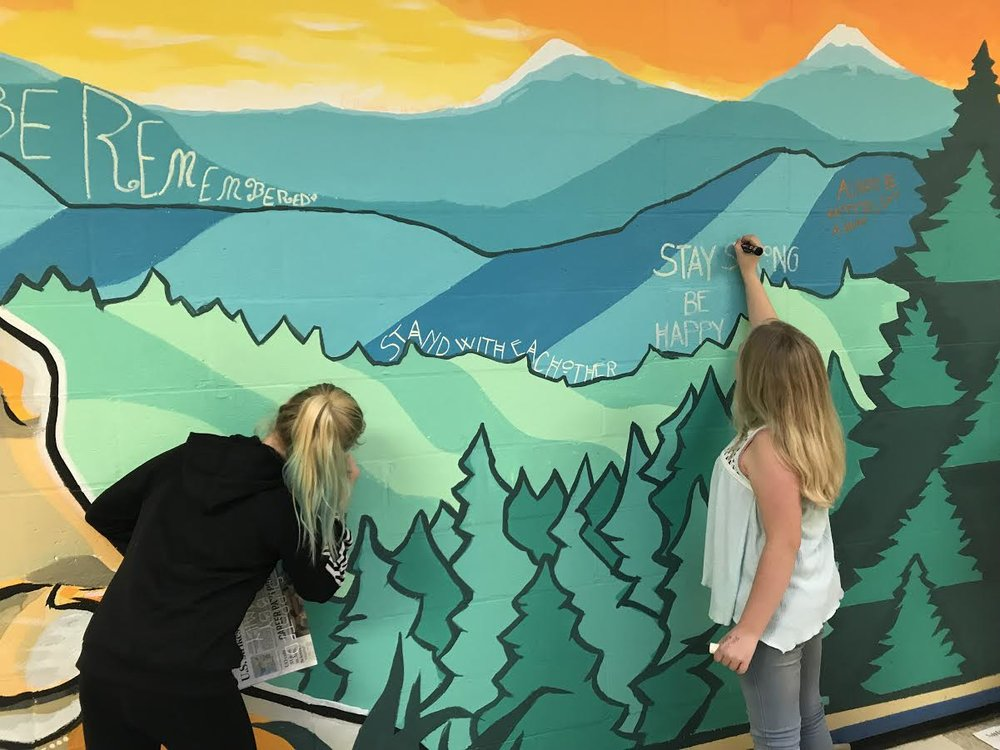 Students at Cascade Middle School add their positive messages to the mural in their school.