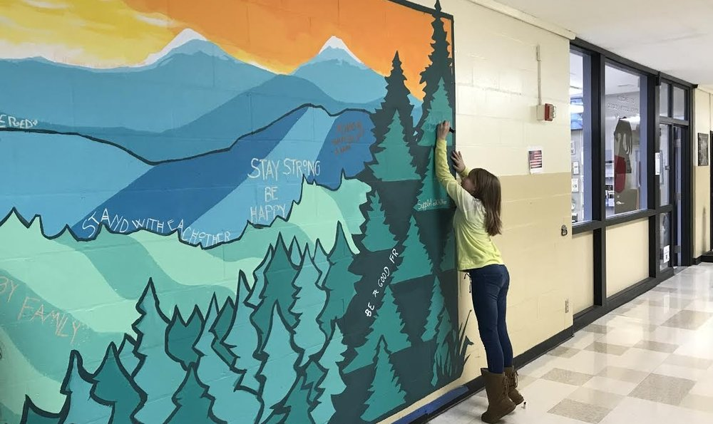 A student stretches to make her mark on the collaborative mural.