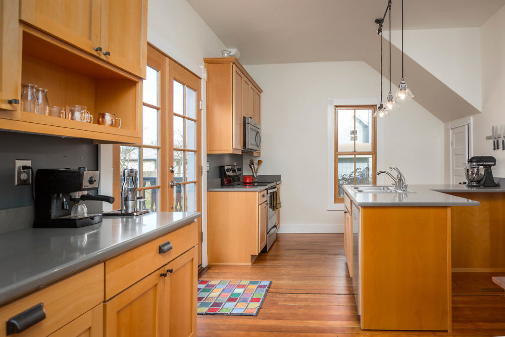 So much character...and storage! Natural light spilling through the many windows...the L-shaped island...stainless steel appliances...plus a walk in pantry...this kitchen has it ALL......