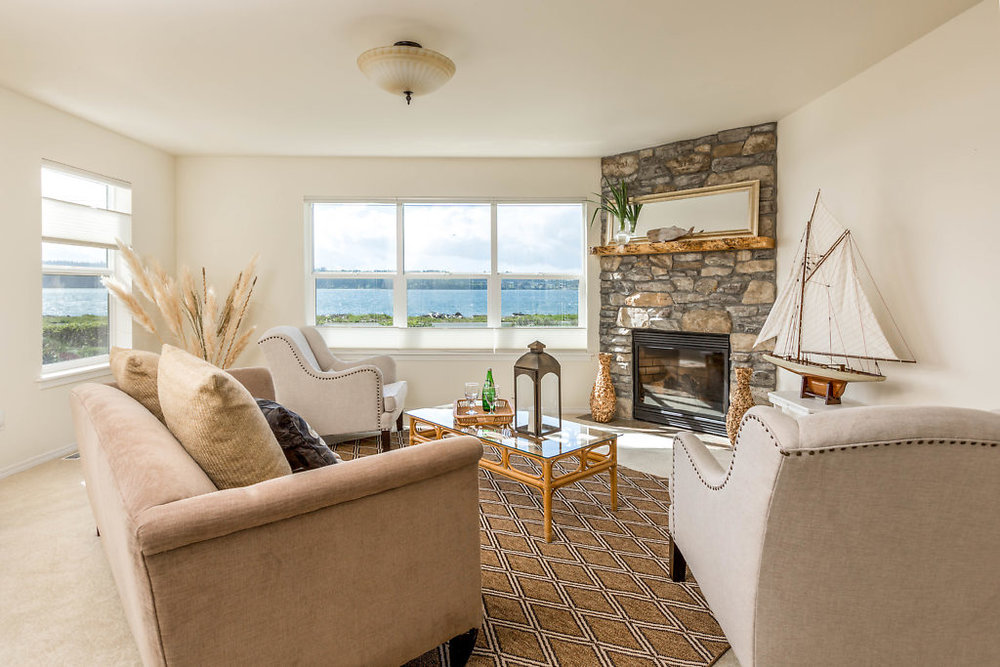 A gorgeous living room with unparalleled Penn Cove & mountain views...curl up by the fireplace in the winter & take your cool drink to the patio in the summer...this home is perfect in any weather....