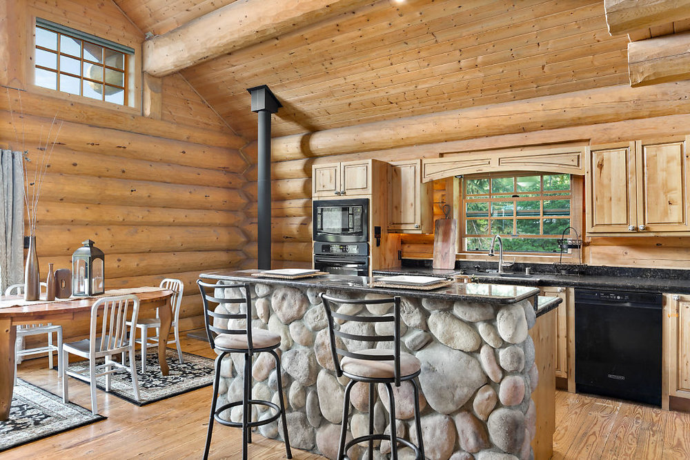 Natural light spills into the custom kitchen complete with granite slab counter-tops, river-rock detailed island, and propane fireplace in the corner....