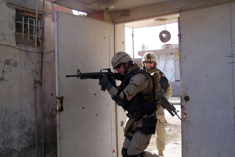 2004:    Builder 1st Class Neil Reno, front, and Construction Electrician 3rd Class Scott Tyner of Navy Reserve Seabees assigned to the Tactical Movement Team (TMT) of Naval Mobile Construction Battalion Two Three (NMCB-23), clear a building prior to an assessment team mission in Fallujah, Iraq. Teams attached to the I Marine Expeditionary Force Engineer Group (I MEG) began conducting assessments on the heels of some of the fiercest fighting since the war's onset. TMT is a mobile engineering and security force, designed to offer Seabee expertise with Marine tactical capabilities. TMT provide security escort formerly only offered by Marine forces. U.S. Navy photo by Chief Journalist Suzanne Speight.