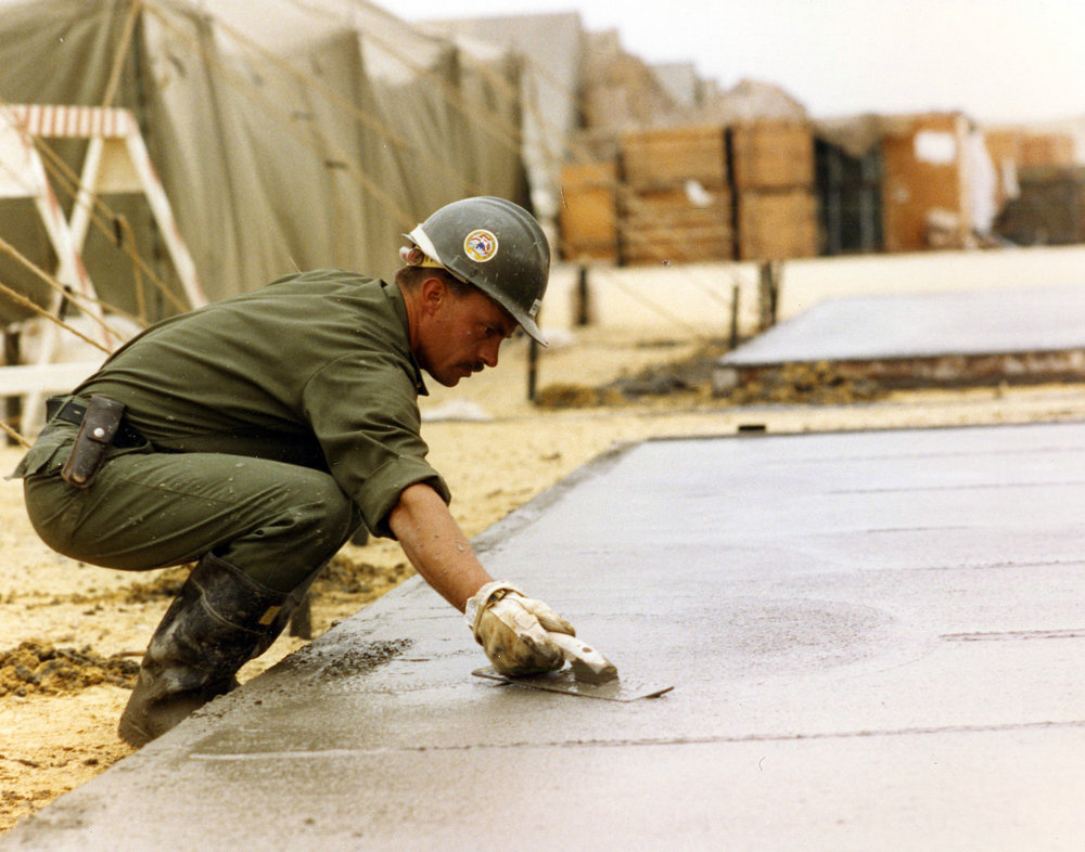 Petty Officer Second Class Michael Cowart smooths concrete during construction of a Marine camp in northern Saudi Arabia. Cowart is a member of the Naval Mobile Construction Battalion Five operating during Operation Desert Storm in February 1991. Photographed by CWO2 Ed Bailey. (NHHC Photograph Collection, Navy Subject Files, Seabees)