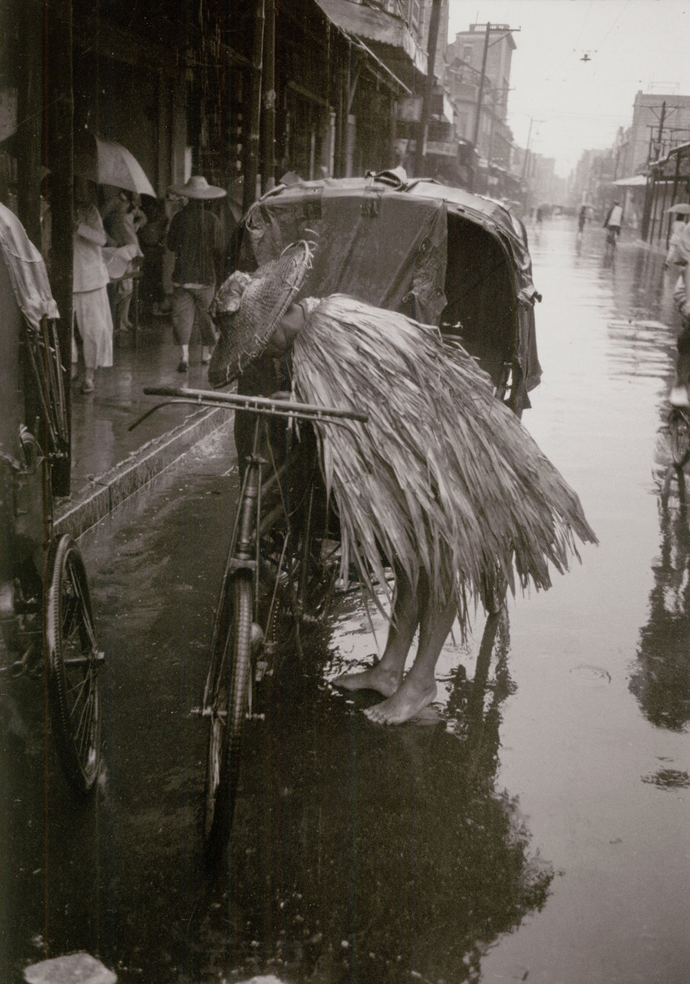 A rain cape of leaves on a pedicab man in Canton. China, May 1956.  (RDH C001-25)