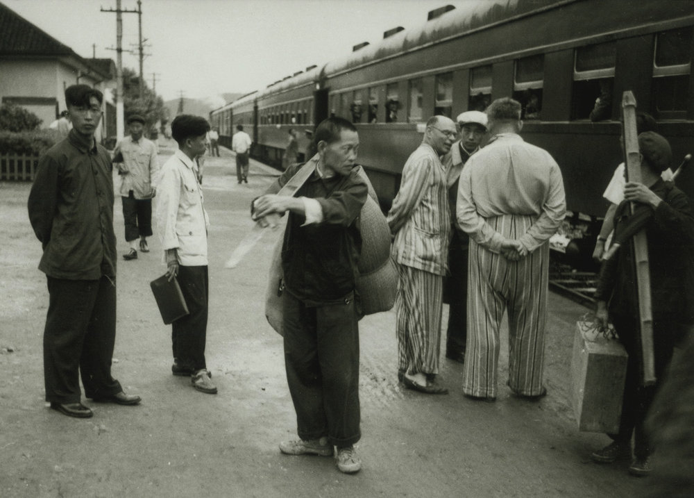 Russians, in their usual daytime travel dress of pyjamas, at a station on the main Canton to Hankow line, China, May 1956. (RDH C105-13a)