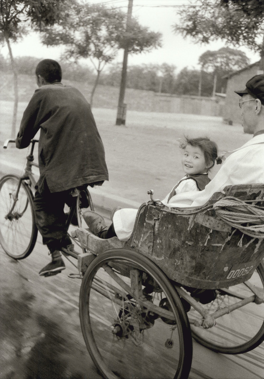 A pretty little girl in a pedicab. Her father was a doctor at the Children's hospital. I was also in a Pedicab and we flirted along Chang An. Peking, China, May 1956. (RDH C025-07)
