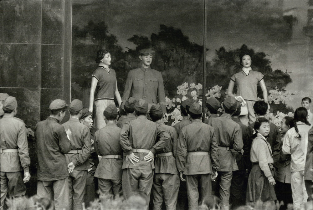 "Soldiers looking at a ""Dress Reform"" display of ""Western fashions"" in the window of a new department store in Wang Fu Chin, Peking. China. 1956. (RDH C014-12)"