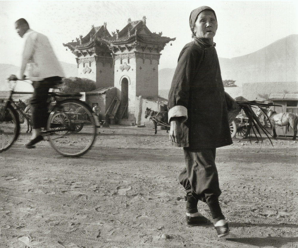 An old lady with bound feet walking in the early morning at Lanchow. China, July 1956.  (RDH R25-06)