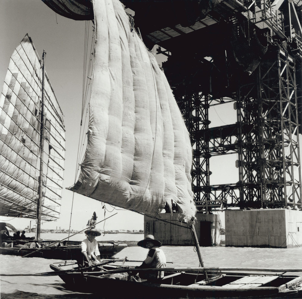 Junks sail under a new Yangtze River bridge being built with new methods at Hankow. China, September 1956. (RDH R35-09)