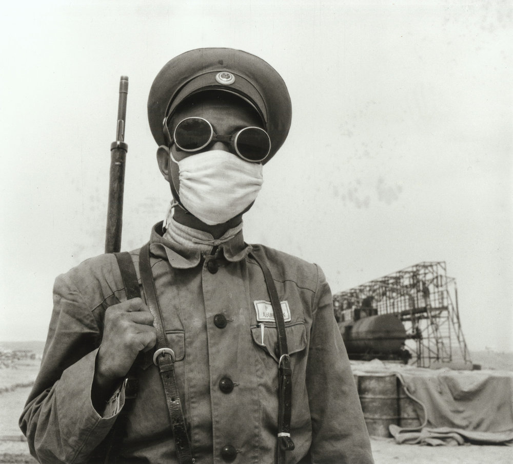 An armed guard at a Yumen oil field wears protection during a dust storm. China, July 1956. (RDH R19-04)