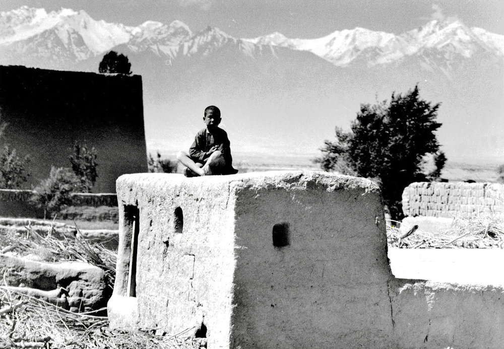 A boy sits on top of a typical Gobi house, in sight of the Tien Shan range in the background. China, July 1956. (RDH C063-27)