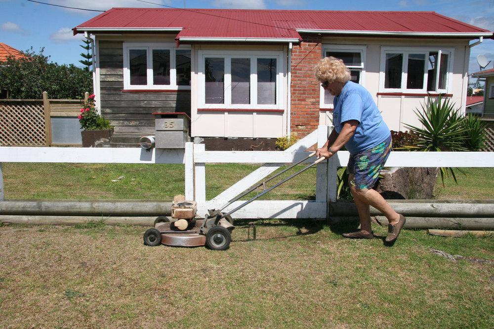 Mrs Brittain mowing her neighbor's lawn, Wharf Road, 3 March 2005. (JBT15)