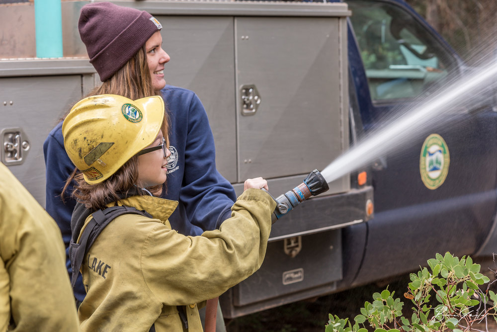 Michelle Cottier a firefighter with ODF geared up Feanix Hightower of Chiloquin Elementary and instructs her how to use the fire hose of  Oregon Department of Forestry  Engine 8150 at the 54th Annual Klamath County Forest Tour. Image:  Brian Gailey