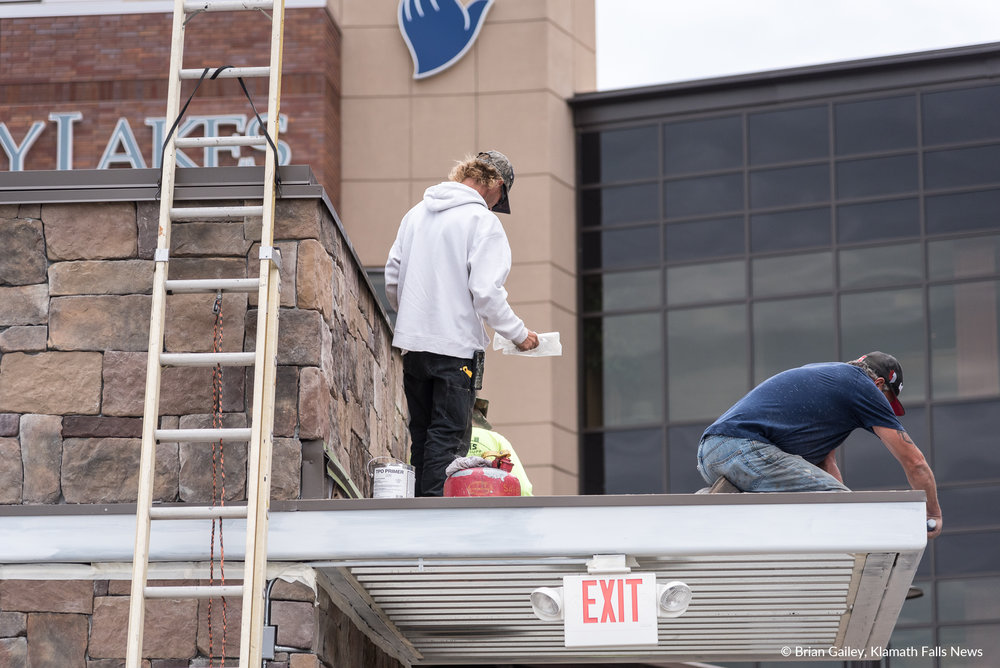 Workers finalize painting on the elevator structure located in the corner of the parking garage near the front entrance to Sky Lakes Medical Center (Brian Gailey)