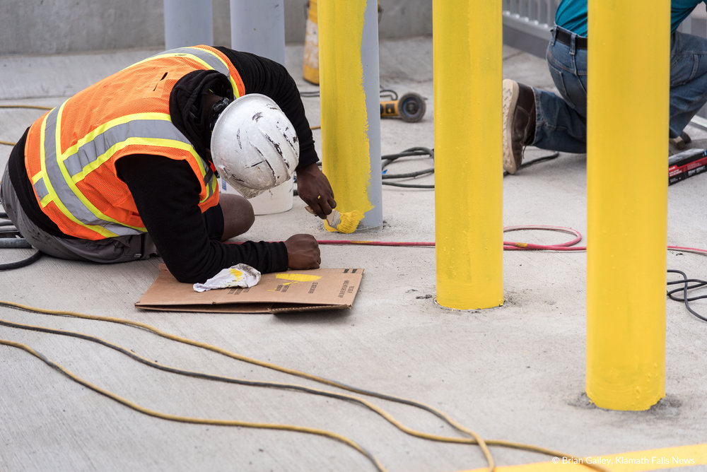 A worker with Perlo Construction paints final touches on a parking bollard. (Brian Gailey)