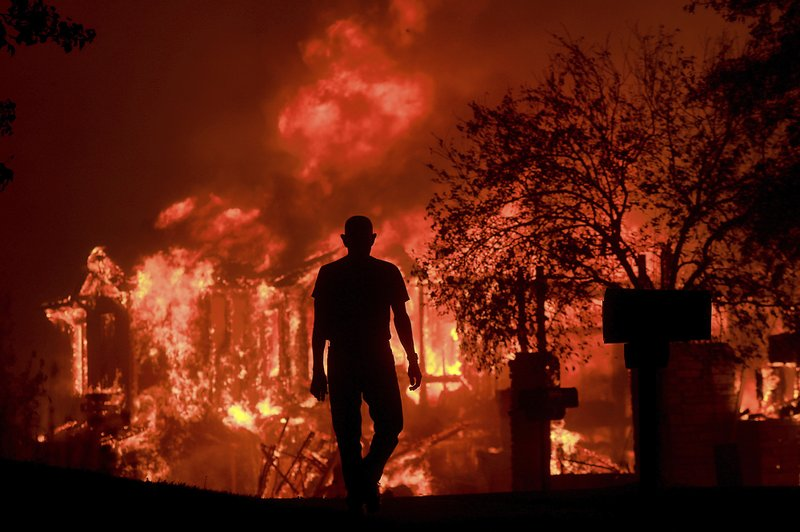 Jim Stites watches part of his neighborhood burn in Fountaingrove, Calif., Monday Oct. 9, 2017. (Kent Porter/The Press Democrat via AP)