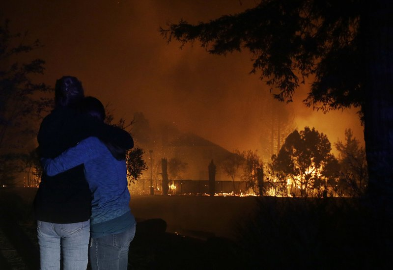 Two women hug as they watch houses burn in Santa Rosa, Calif., Monday, Oct. 9, 2017. (AP Photo/Jeff Chiu)