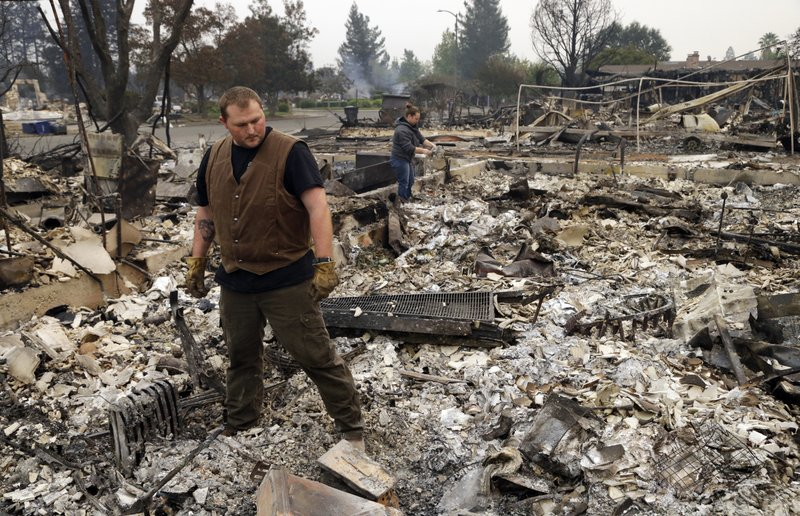 Luke Baier, left, and his wife Gina Baier look through the remains of their home in the Coffey Park area of Santa Rosa, Calif., on Tuesday, Oct. 10, 2017. (AP Photo/Ben Margot)