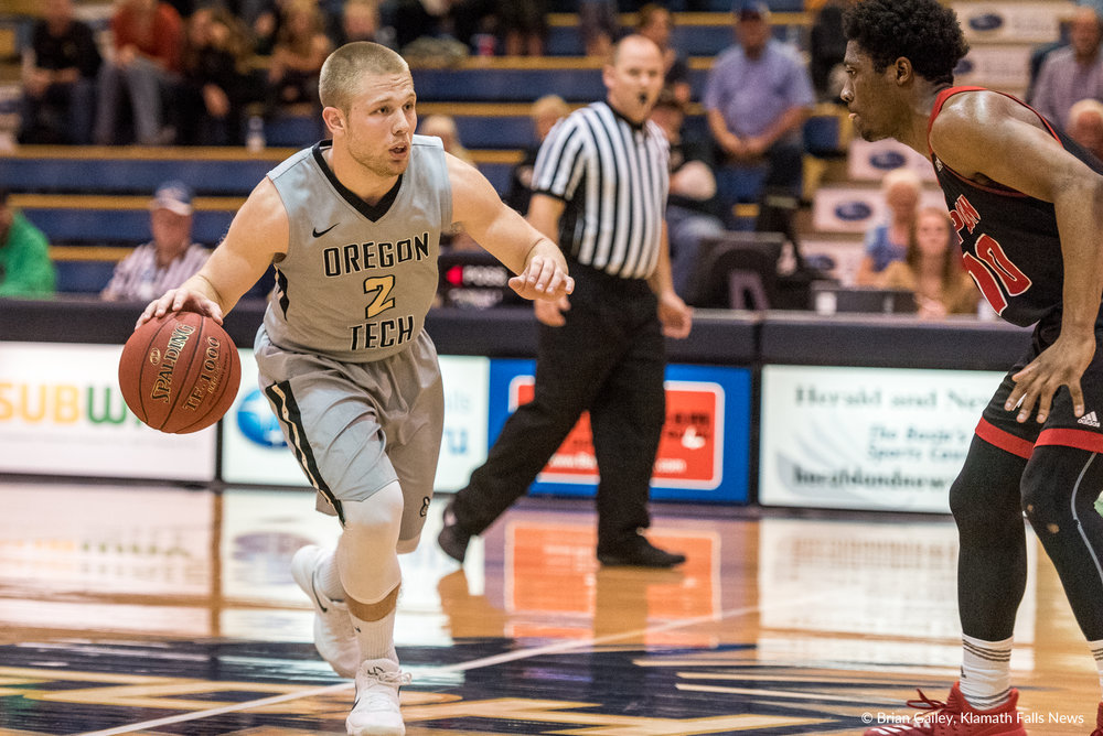 OIT Guard Mitchell Fink #2 drives against a defender from Simpson University. Fink had 11 points on the night. (Brian Gailey)
