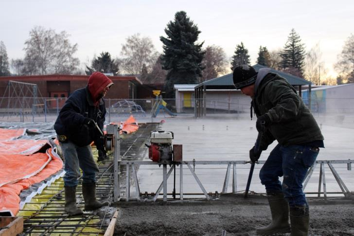 Workers smooth a concrete pad use as a foundation for new classrooms at Peterson Elementary School (Samantha Tipler, KCSD)