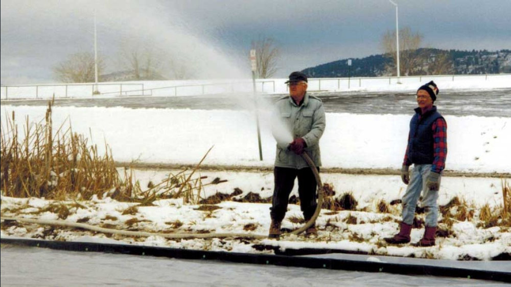 Bill Collier spraying the first layer of water with a fire hose while Glenn Gailis looks on.  This was the original Bill Collier Community Ice Arena in Moore Park - the first year we put down a plastic liner over the dirt patch. (KlamathIceSports.org)