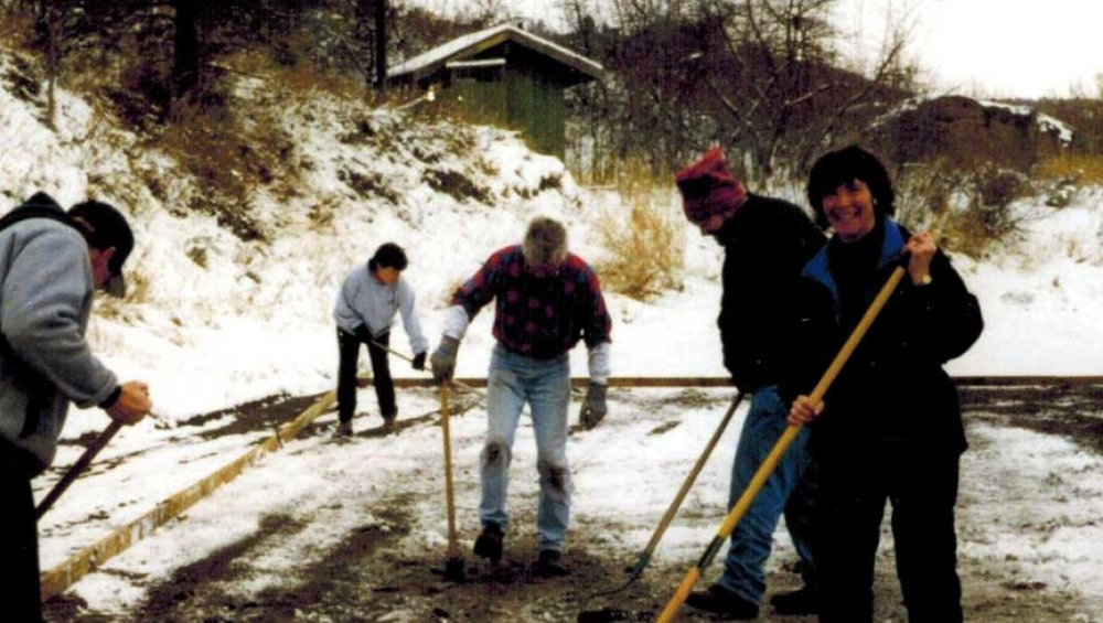 In the late 1990's, volunteers raking the sand and leveling it prior to putting down the plastic liner.  Led by our very own Paulamom - right-hand side. (KlamathIceSports.org)